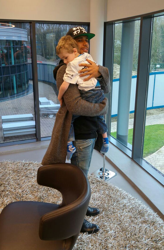 Lewis Hamilton cradling Harry Newman at the race headquarters in Brackley, Northamptonshire.